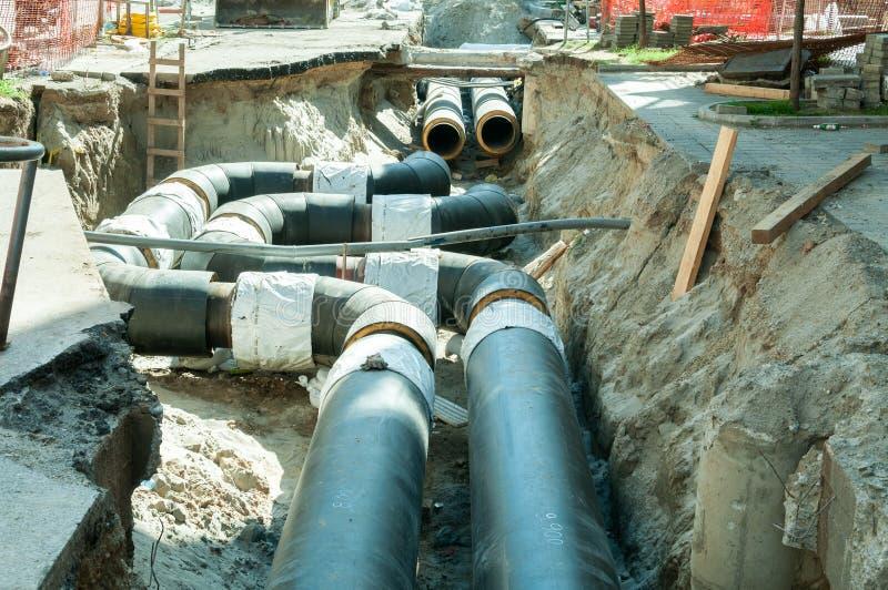 Ricostruzione e sostituzione del sistema sotterraneo del riscaldamento centrale di un quartiere nella città con i nuovi tubi fotografia stock libera da diritti