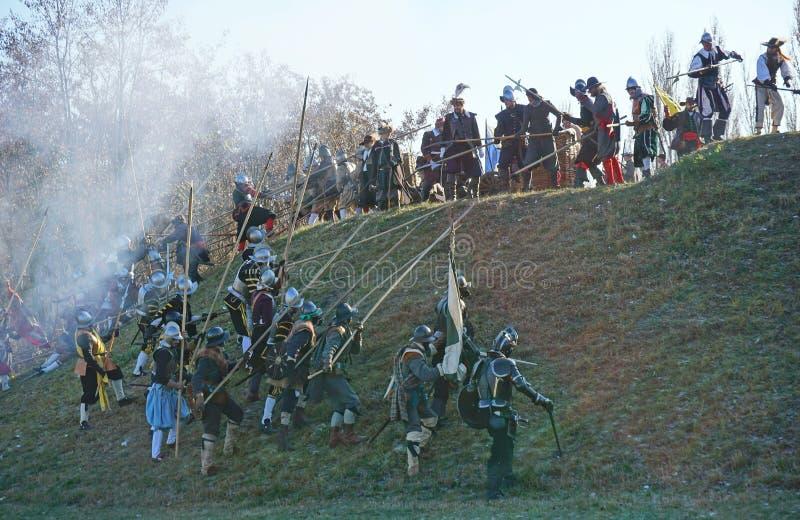 Ricostruzione storica di battaglia - attaccanti che eseguono su una collina contro le protezioni fotografia stock