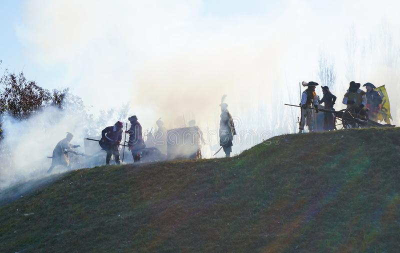 Ricostruzione storica di battaglia - i soldati con i cannoni sono in fumo su una collina immagini stock