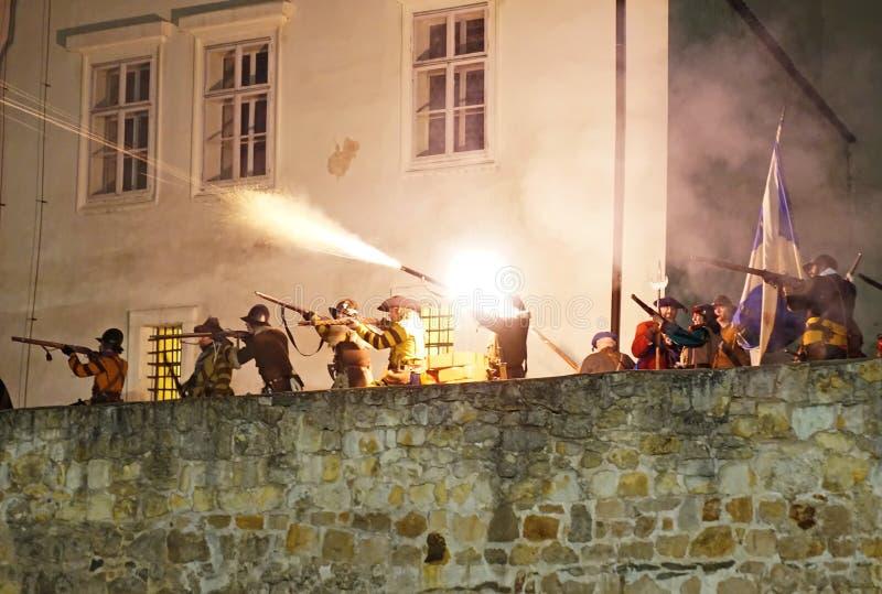 Ricostruzione storica di battaglia - moschettieri su una fucilazione del bastione alla notte immagine stock libera da diritti