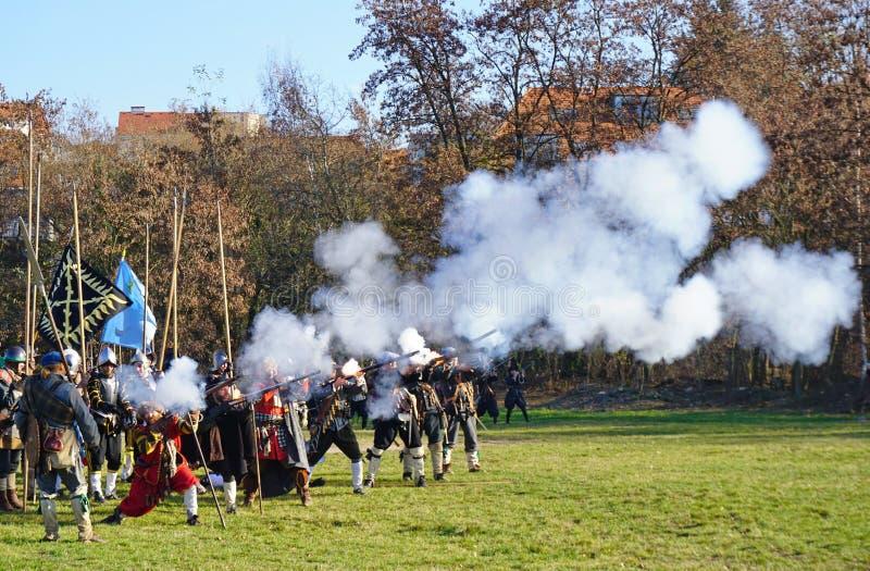 Ricostruzione storica di battaglia - moschettieri in una fucilazione di fila su un campo verde immagine stock libera da diritti