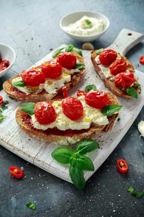 A ricota Bruschetta do tomate com sol secou a pasta de tomates, o pão de mistura do azeite e a manjericão imagens de stock