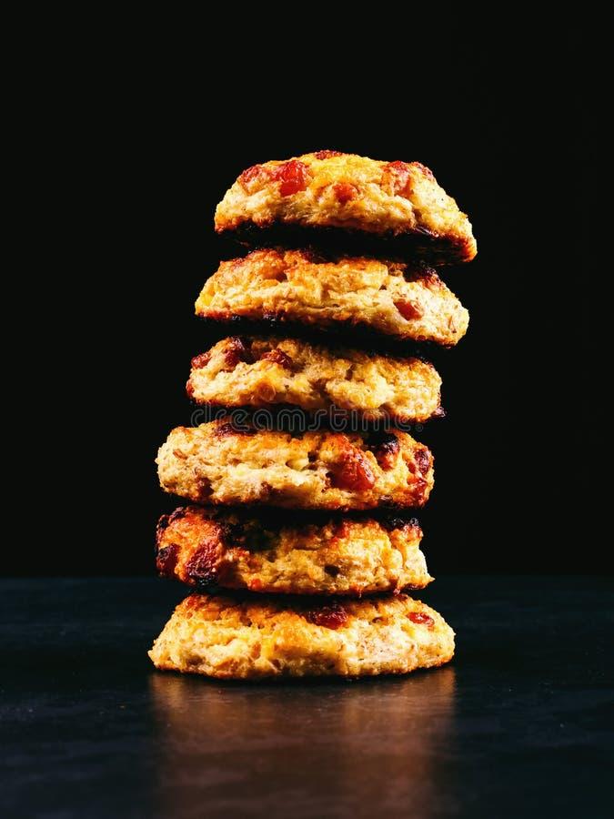 Ricotta al forno e biscotti di farina d'avena con l'uva passa Nutrizione sana, alimento di dieta Pila su un fondo nero fotografia stock