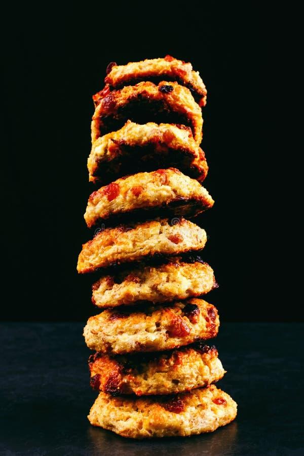 Ricotta al forno e biscotti di farina d'avena con l'uva passa Nutrizione sana, alimento di dieta Pila su un fondo nero immagine stock libera da diritti