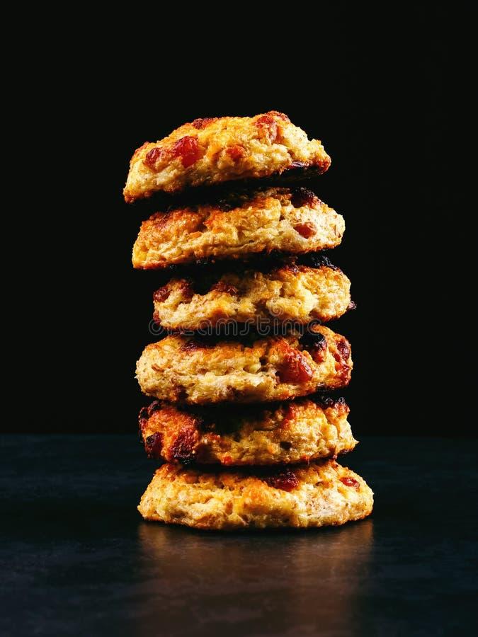 Ricotta al forno e biscotti di farina d'avena con l'uva passa Nutrizione sana, alimento di dieta Pila su un fondo nero fotografie stock libere da diritti