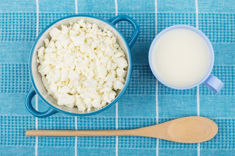 Ricotta in ciotola blu, tazza di latte e cucchiaio fotografia stock libera da diritti