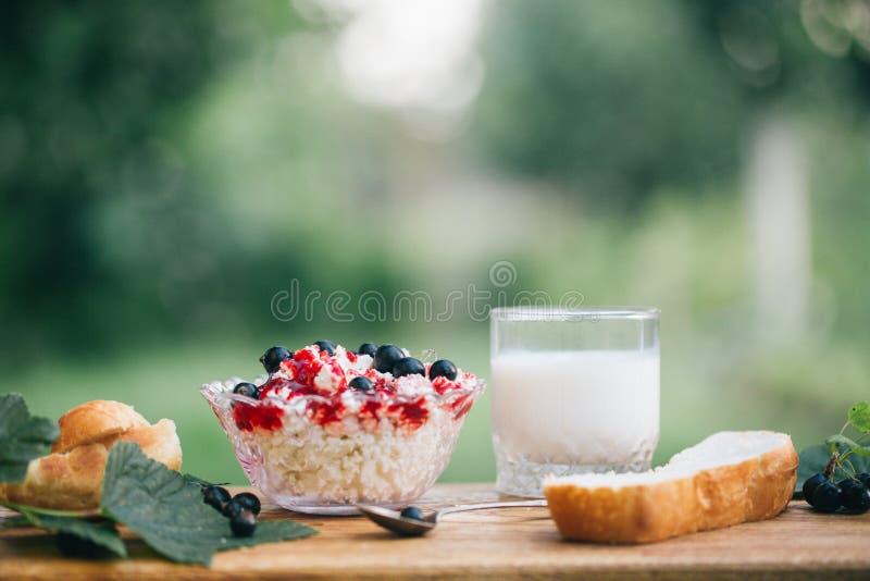 Ricotta con l'inceppamento della bacca con il ribes nero fresco, un bicchiere di latte e una fetta di pane di recente al forno su fotografie stock