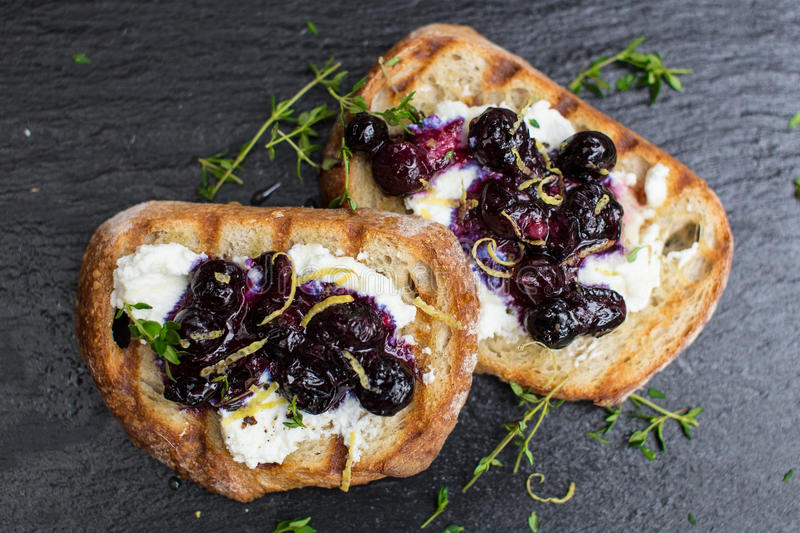 Ricotta toast with blueberry compote. Honey and thyme stock images