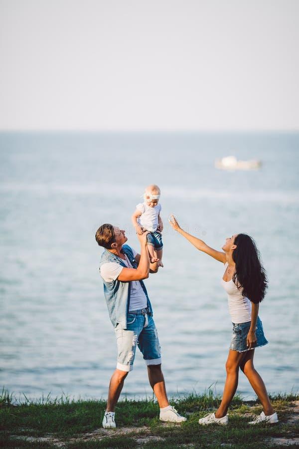 Ricreazione all'aperto della famiglia con le viste del mare giovane famiglia caucasica con il bambino di un anno in armi, vestiti fotografie stock