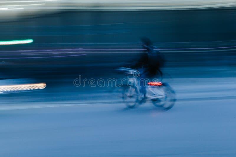 Rida en cykel i en suddig stadsplats royaltyfri foto