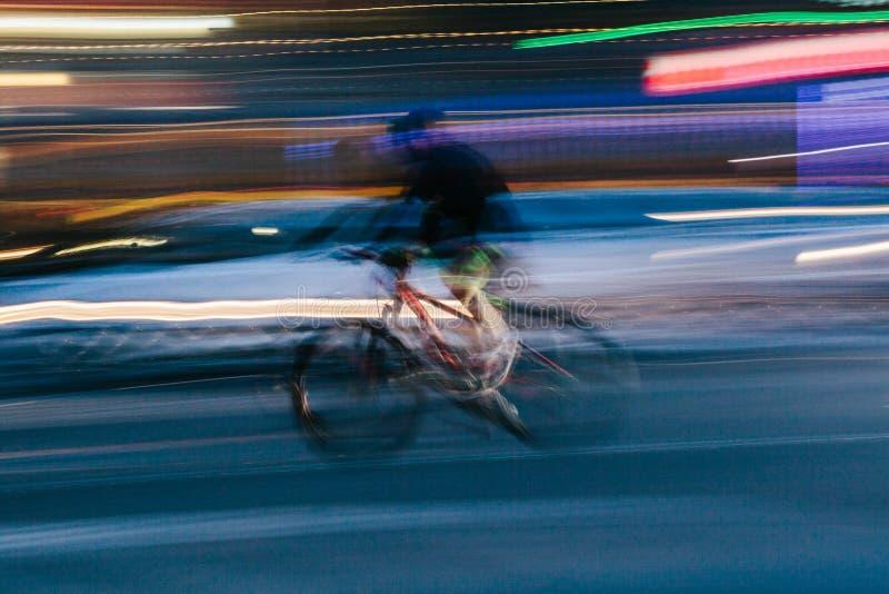 Rida en cykel i en suddig stadsplats royaltyfri fotografi