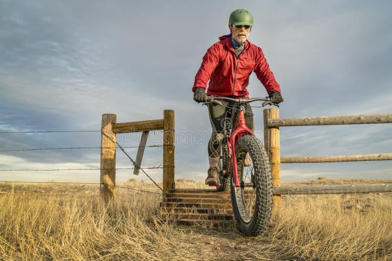 Rida en fet cykel för berg över färisten arkivbilder
