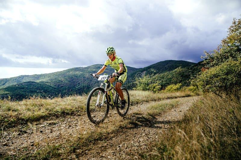 Rida för kvinnaryttarecyklist som är stigande på en bakgrund av berg och moln arkivfoton