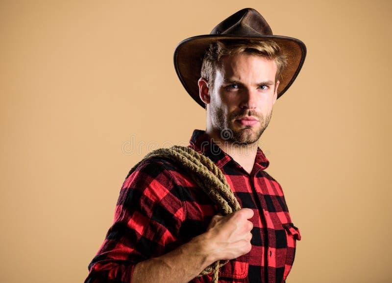 Rida vilken häst som helst Vintage style man man Wild West retro cowboy man schackade skjorta på ranch vildlevande västerländsk r royaltyfri bild