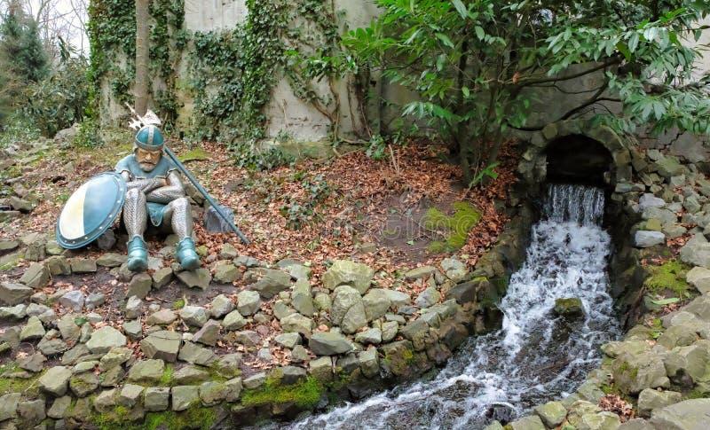 Riddare som sitter nära en liten vik med vattenfallet bak slott royaltyfri foto