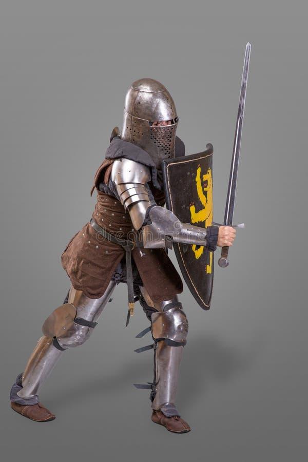 Ridder in adem in een helm met een zwaard en schild in slag over grijze achtergrond stock afbeelding