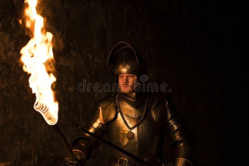 Ridder met een toorts en zwaard bij nacht op een muurachtergrond stock afbeeldingen