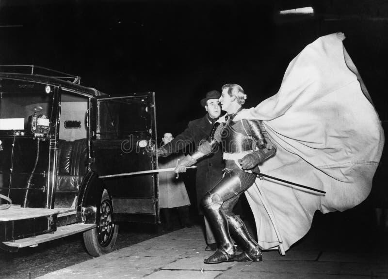 Ridder met golvende kaap naderbij komende auto royalty-vrije stock fotografie