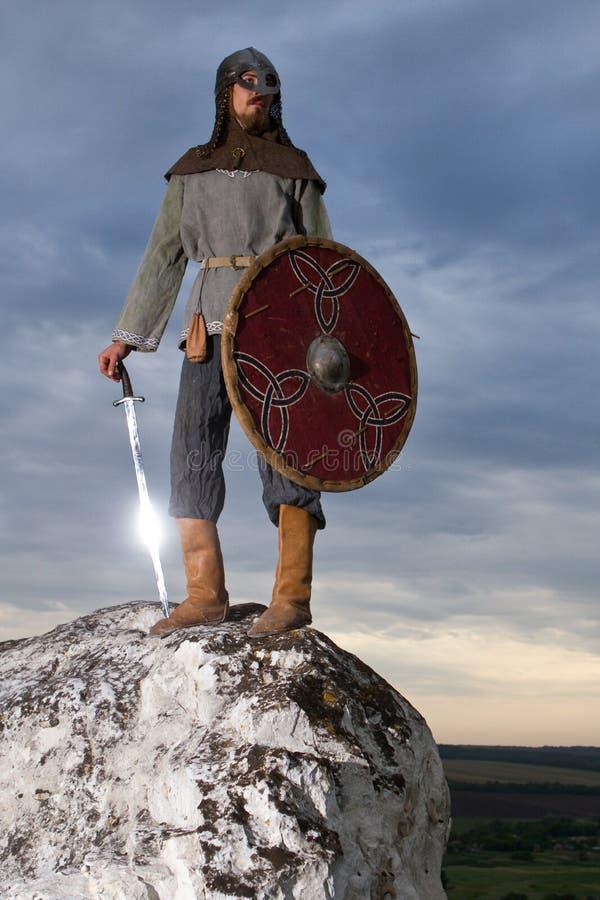 Ridder op een rots met een zwaard stock afbeelding