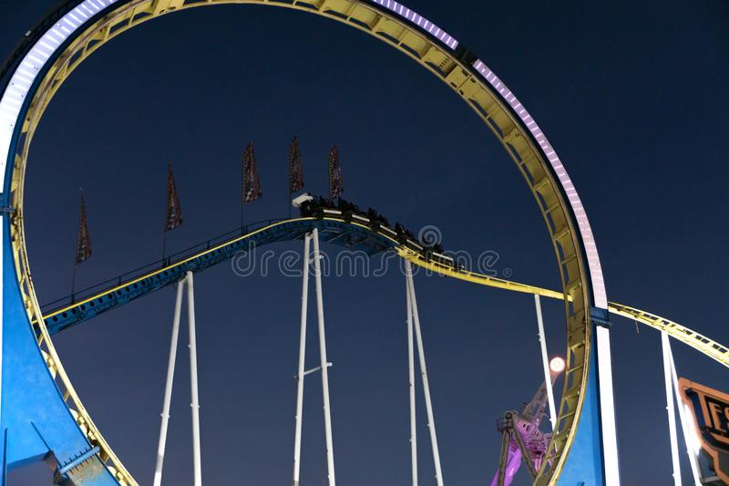 Ride on an illuminated large roller coaster with loop royalty free stock photos