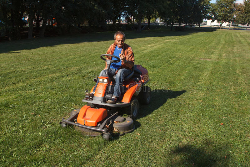 Ride-on lawn mower cutting grass. stock photos