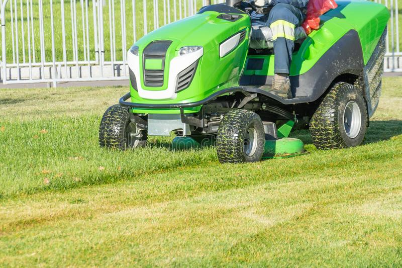 Ride lawn mower mows a green fresh grass.  royalty free stock photography