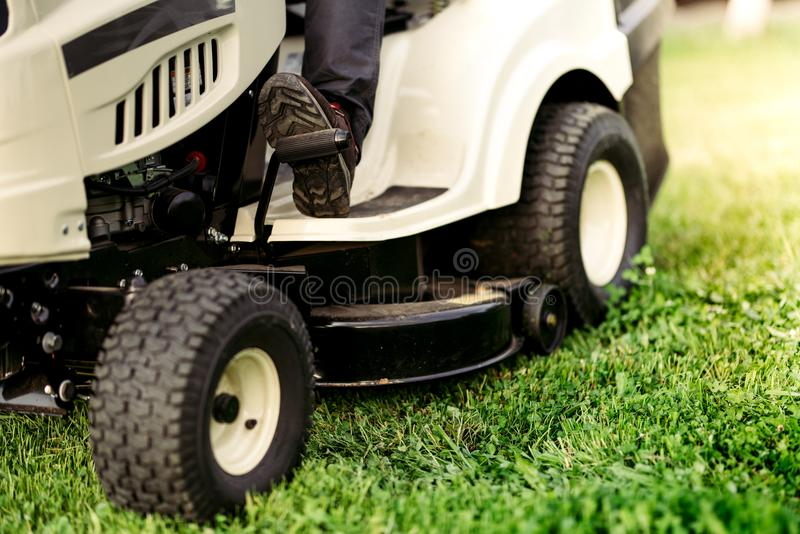 Ride-on lawnmower close up details of cutting grass. Landscaping industrial. Details stock image