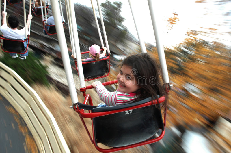 Ride in motion. Girl looks at camera as ride is in motion