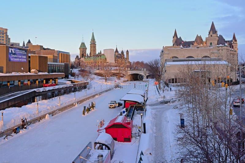 Ridea kanal som täckas i snö, med NAC, parlamentkullen och den Fairmont Château Laurier slotten royaltyfri foto