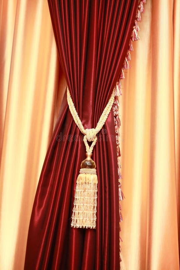 Rideau pourpré en velours avec le gland d'or photo stock