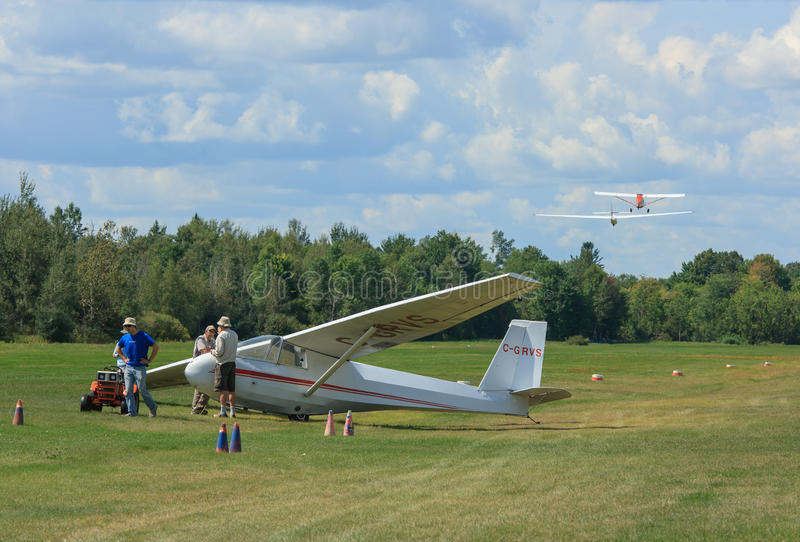 Rideau Valley Soaring Club. MANOTICK, CANADA – AUGUST 19: Gliders, one being towed and one on the airstrip, at Rideau Valley Soaring on August 19, 2012 in royalty free stock photography