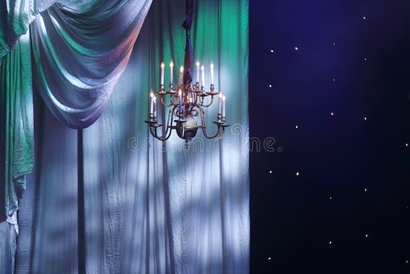 Rideaux avec l'éclairage bleu-vert et le lustre photos libres de droits