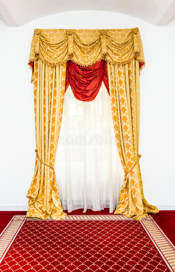Rideaux jaunes dans la chambre avec le tapis rouge photographie stock libre de droits