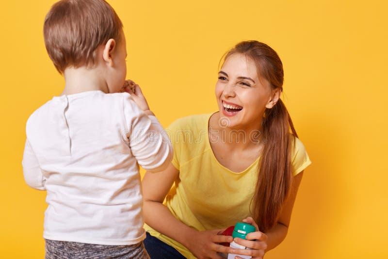 Ridendo i giochi allegri della donna con la sua piccola figlia sveglia, passa insieme il tempo libero sui fine settimana Una giov immagini stock