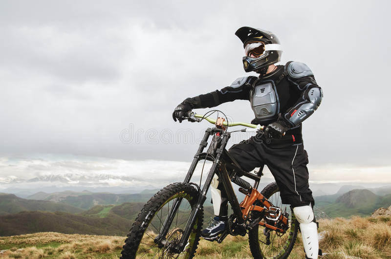 The rider in the full-face helmet and full protective equipment on the mtb bike stands on a rock against the background. The rider in full protective equipment stock photography