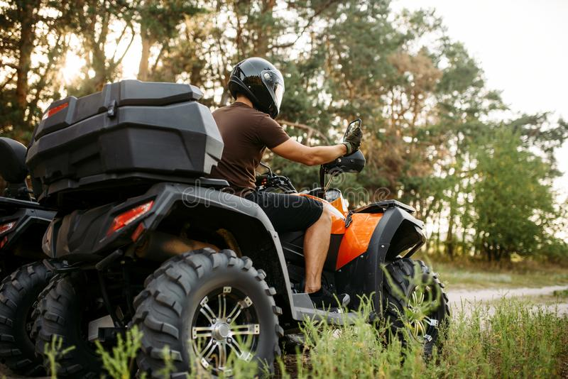 Rider in helmet on quad bike, front view, closeup stock images