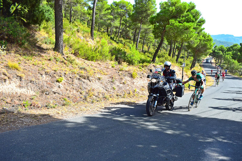 Cycle Racer Being Towed By Motorcycle La Vuelta España. A rider hitches a ride up the hill at the end of stage eight Xorret De Cati in the 2017 La Vuelta Espa royalty free stock photography
