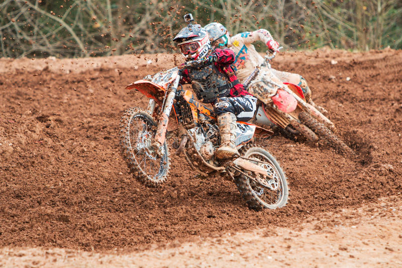 Rider Pops Wheelie Accelerating Through Muddy Turn In Motocross Race royalty-vrije stock fotografie