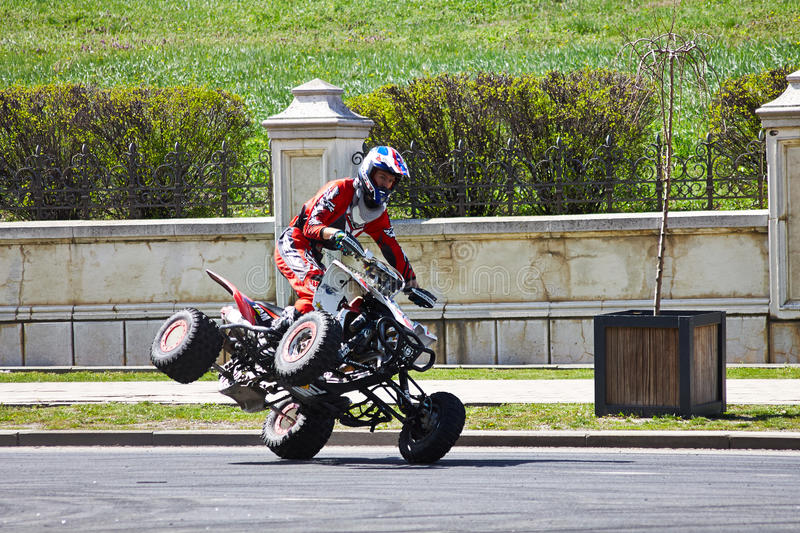 Rider with the quad on 2 wheels stock image