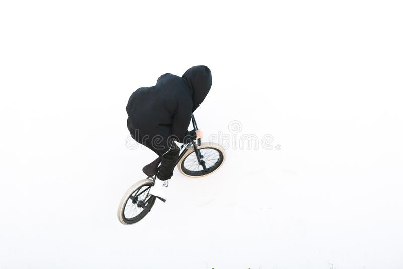 Rider`s back in dark clothes riding a white wall on a bmx bike. bmx trick on a white background stock images