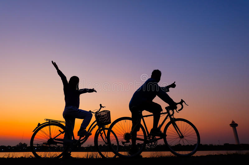 Riders cycling against sunset in silhouette with lots of negative space and dramatic sky. Riders cycling against sunset and sunrise royalty free stock photography