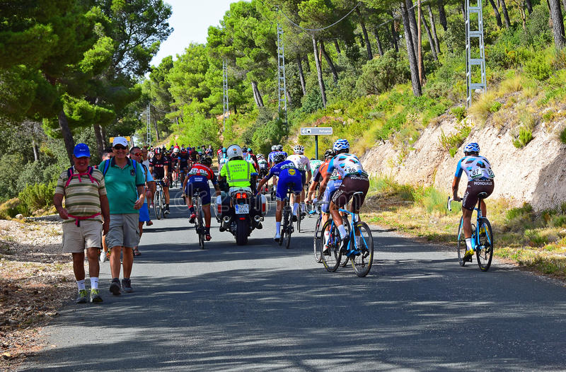 Riders Holding Onto Police Motorcycle La Vuelta España. Riders getting a tow up the hill after stage eight Xorret De Cati in the 2017 La Vuelta España bike royalty free stock photos