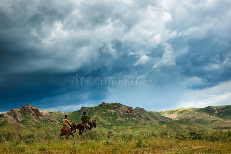 Riders on horseback. Summer pastures in an intermontane valley. Kazakhstan royalty free stock image