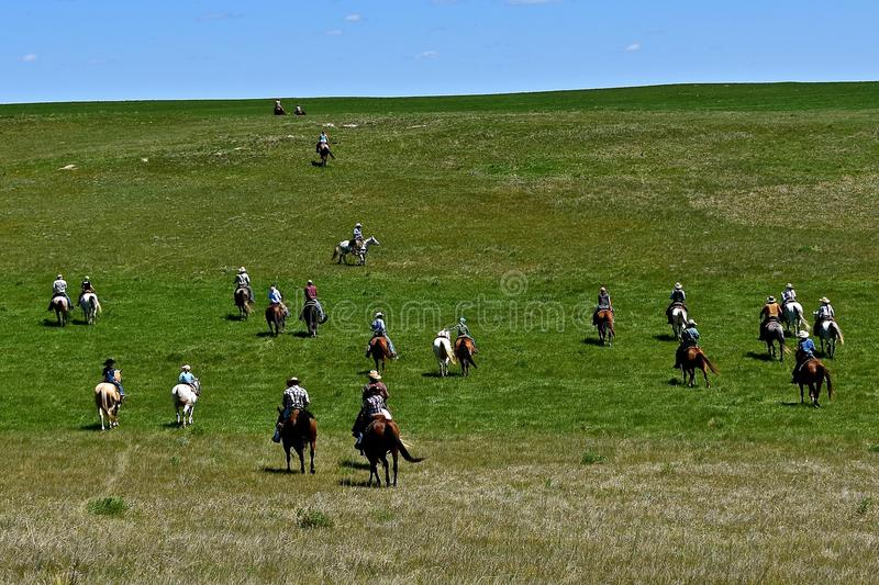 Riders and horses headed to a roundup. Unidentified cowboys and cowgirls ride over the prairies headed to a roundup and branding session royalty free stock photo