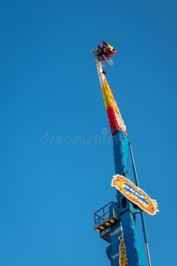 High scary spinning ride in amusement park. Riders on the scary ride high in the air on a sunny day in an amusement park in London royalty free stock photos