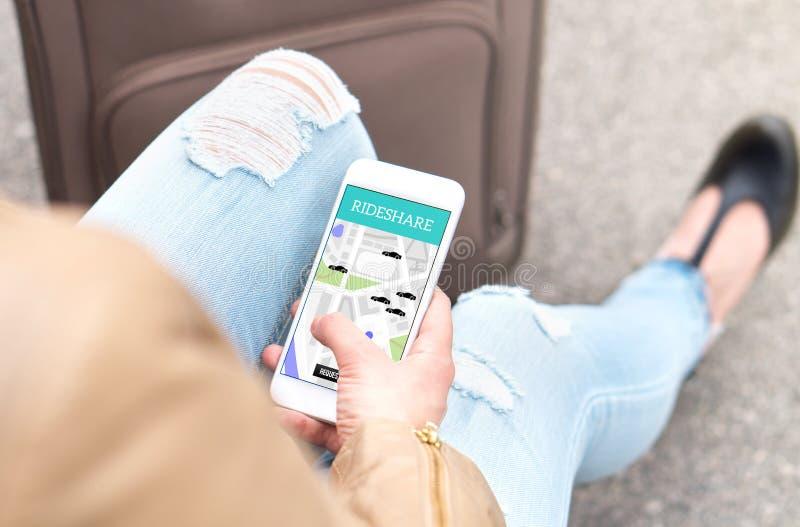 Rideshare app no smartphone Jovem mulher que usa o passeio que compartilha do app imagem de stock