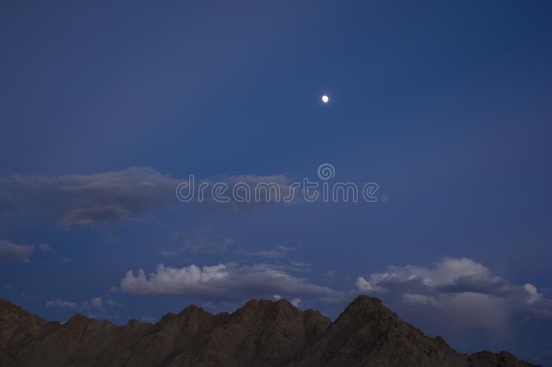 Ridge of gray brown desert mountains under a dark blue evening sky with gray clouds and a full moon with stars royalty free stock photo