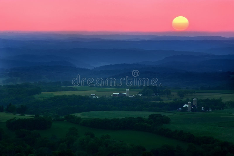Ridges and Valleys. A beautiful rural landscape showing hills and valleys layered and filled with fog during a summer sunset royalty free stock images