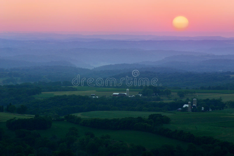 Ridges and Valleys. A beautiful rural landscape showing hills and valleys layered and filled with fog during a summer sunset stock photography