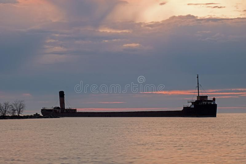 The Ridgeway Great Lakes Freighter At Port Credit, Ontario. The sunrise over Lake Ontario at Port Credit, Ontario, part of the city of Mississauga. The ship is royalty free stock photography